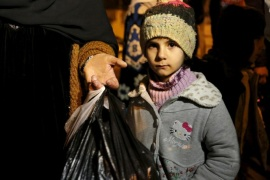 A Syrian girl waits with her family, who say they have received permission from the Syrian government to leave the besieged town, as they depart after an aid convoy entered Madaya, Syria January 11, 2016.  An aid convoy entered a besieged Syrian town on Monday where thousands have been trapped without supplies for months and people are reported to have died of starvation. Trucks carrying food and medical supplies reached Madaya near the Lebanese border and began to distribute aid as part of an agreement between warring sides, the United Nations and the Red Cross said. REUTERS/Omar Sanadiki