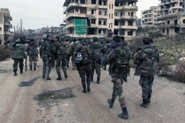 In this photo released on Tuesday, Jan 12, 2016, by the Syrian official news agency SANA, shows Syrian government troops and allied militiamen walk inside the key town of Salma in Latakia province, Syria. Syrian troops and allied militiamen are expanding their area of control around an insurgent stronghold in the northwestern province of Lattakia after seizing the key town of Salma a day earlier. (SANA via AP)