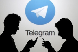 Two men pose with smartphones in front of a screen showing the Telegram logo in this picture illustration taken in Zenica, Bosnia and Herzegovina November 18, 2015. The mobile messaging service Telegram, created by the exiled founder of Russia's most popular social network site, has emerged as an important new promotional and recruitment platform for Islamic State. The service, set up two years ago, has caught on in many corners of the globe as an ultra-secure way to quickly upload and share videos, texts and voice messages. It counts 60 million active users around the world. Picture taken November 18.     REUTERS/Dado Ruvic