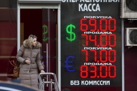 A woman walks at an exchange office sign showing the currency exchange rates of the Russian ruble, U.S. dollar, and euro in Moscow, Russia, Tuesday, Dec. 29, 2015. The Russian ruble continued its decline on Tuesday, dropping by 0.6 percent to 72.6 rubles to the dollar. (AP Photo/Alexander Zemlianichenko)
