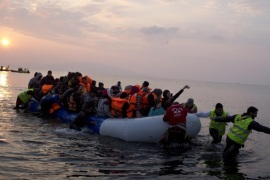 Volunteers help migrants and refugees on a dingy as they arrive at the shore of the northeastern Greek island of Lesbos, after crossing the Aegean sea from Turkey on Sunday, March 20, 2016. In another incident two Syrian refugees have been found dead on a boat on the first day of the implementation of an agreement between the EU and Turkey on handling the new arrivals. (AP Photo/Petros Giannakouris)