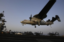 FILE – In this Aug. 10, 2014 file photo, an aircraft lands after missions targeting the Islamic State group in Iraq from the deck of the U.S. Navy aircraft carrier USS George H.W. Bush in the Persian Gulf. (AP Photo/Hasan Jamali, File)