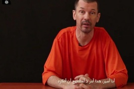 "FILE – In this file still image taken from an undated video published on the Internet by Al-Furqan, the media arm of the Islamic State group militants, captive British journalist John Cantlie speaks into the camera on the first of what he says will be a series of lecture-like ""programs"" in which he says he will reveal ""the truth"" about the Islamic State group. The British photojournalist has been used by the Islamic State group to take on the role of a war correspondent. He has appeared in several videos delivering statements, purportedly from Kobani and Mosul, likely under duress. Cantlie has worked for several publications including The Sunday Times, The Sun and The Sunday Telegraph. The Arabic subtitle reads ""I am a prisoner and that is something I will not deny."" (AP Photo, File)"