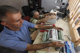 Men count wads of Iraqi dinars using money counting machines at a currency exchange shop in Baghdad October 1, 2012. Many Iraqis have lost faith in their dinar currency but to some foreign speculators, it promises big profits. The contrast underlines the uncertainties of investing in Iraq as the country recovers from years of war and economic sanctions. Picture taken October 1, 2012. To match IRAQ-ECONOMY/DINAR REUTERS/Saad Shalash (IRAQ – Tags: BUSINESS POLITICS)