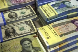 FILE–In this Saturday, April 4, 2015 file photo, Iranian and U.S. banknotes are on display at a currency exchange shop in downtown Tehran, Iran. Iran said Tuesday, Jan. 19, 2016,  it successfully transferred some of the billions of dollars' worth of frozen overseas assets following the implementation of the nuclear deal with world powers. But ordinary Iranians are still waiting to see how their daily lives will improve and how fast Iranian companies will gain access to financial markets worldwide. (AP Photo/Vahid Salemi,File)