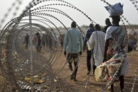 "FILE- In this file photo taken Tuesday, Jan. 19, 2016,displaced people walk next to a razor wire fence at the United Nations base in the capital Juba, South Sudan. A U.N. report describing sweeping crimes like children and the disabled being burned alive and fighters being allowed to rape women as payment shows South Sudan is facing ""one of the most horrendous human rights situations in the world,"" the U.N. human rights chief said Friday, March 11, 2016. (AP Photo/Jason Patinkin, File)"