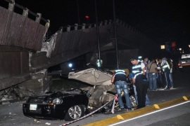 Members of Ecuadoran emergency services check a car after a bridge collapsed due to a 7.8 magnitude earthquake, in the city of Guayaquil, Ecuador, late 16 April 2016. At least 77 people were killed and hundreds injured in an earthquake affecting the Ecuadoran northern coastal region.