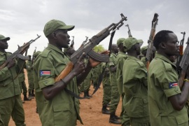South Sudanese rebel soldiers raise their weapons at a military camp in the capital Juba, South Sudan, Thursday, April 7, 2016. South Sudan's rebels have set up camp at two designated sites in the capital as part of the process to secure the city for their leader Riek Machar's return later this month, and eventually reintegrate into the split army, after over two years of war. (AP Photo/Jason Patinkin)