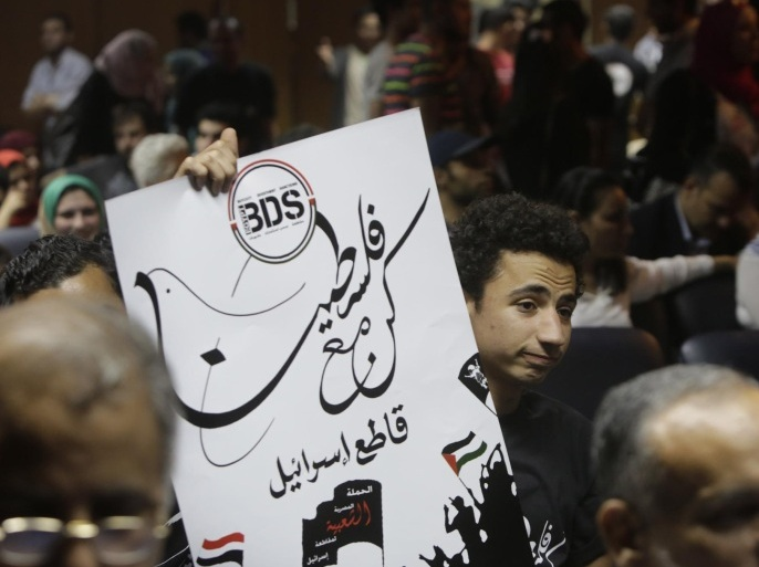 "An Egyptian raises a poster with the Boycott, Divestment and Sanctions (BDS) logo and Arabic that reads, ""we are all with Palestine, boycott Israel,"" during the launch of the Egyptian campaign that urges boycott, divestment and sanctions against Israel and Israeli-made goods, at the Egyptian Journalists' Syndicate in Cairo, Egypt, Monday, April 20, 2015. BDS is a global movement initiated by Palestinian civil society activists in 2005 that organizers say will continue until Israel complies with international law and respects Palestinian rights. (AP Photo/Amr Nabil)"