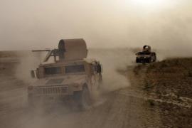 FILE – Iraqi army Humvees race toward the front lines on the outskirts of Ramadi during heavy clashes with Islamic State group militants in this Sept. 12, 2015, file photo. The fighting eventually led to the recapture of the city from the extremists. After the massive destruction wreaked on Ramadi, Iraqi and coalition officials are rethinking tactics as they prepare for an assault to retake the biggest IS-held prize, the northern city of Mosul. (AP Photo, File)