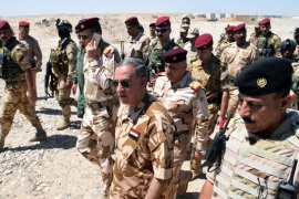 Iraqi Defence Minister Khaled al-Obaidi (C) walks with Iraqi army officers during his visit to the military forces in western Fallujah city, west of Iraq, 11 June 2016. According to Iraqi officials, Iraqi troops backed by airstrikes carried out by the international anti-IS coalition to liberate Nassaf area west of Fallujah city, from the hands of the Islamic State (IS).