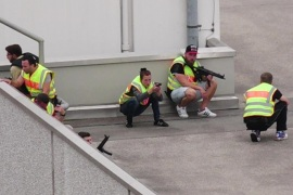 A screen grab taken from video footage shows plain clothes police officers taking cover in the car park of the Olympia shopping mall during shooting rampage in Munich, Germany July 22, 2016.  dedinac/Marc Mueller/handout via REUTERS  NO ARCHIVES. FOR EDITORIAL USE ONLY. NOT FOR SALE FOR MARKETING OR ADVERTISING CAMPAIGNS. THIS IMAGE HAS BEEN SUPPLIED BY A THIRD PARTY. IT IS DISTRIBUTED, EXACTLY AS RECEIVED BY REUTERS, AS A SERVICE TO CLIENTS.  TPX IMAGES OF THE DAY