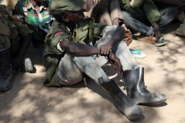 Rebel child soldiers gather in Gumuruk, as they prepare to handover their weapons at a demobilisation ceremony in Jonglei State, eastern South Sudan, January 27, 2015. The teenage rebel soldiers watched as their comrades handed over their assault rifles and stripped off their oversized khaki uniforms with the red, black and green South Sudan flag emblazoned on the right shoulder. Picture taken January 27, 2015.   To match story SOUTHSUDAN-CHILD SOLDIERS/      REUTERS/Ka
