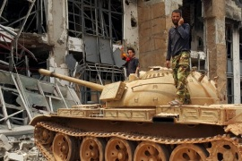 Members of the Libyan pro-government forces stand on a tank in Benghazi, Libya, May 21, 2015. Libya, which has descended into near anarchy since NATO warplanes helped rebels overthrow former dictator Muammar Gaddafi in a 2011 civil war, is now the third big stronghold for Sunni Islamist group Islamic State, also known as ISIS or ISIL, which declared a Caliphate to rule over all Muslims from territory it holds in Syria and Iraq. REUTERS/Stringer