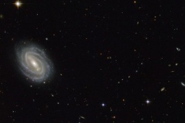 An undated handout picture made available by NASA on 08 September 2014 shows a NASA and European Space Agency (ESA) Hubble Space Telescope image of a spiral galaxy known as PGC 54493, located in the constellation of Serpens (The Serpent). This galaxy is part of a galaxy cluster that has been studied by astronomers exploring an intriguing phenomenon known as weak gravitational lensing. This effect, caused by the uneven distribution of matter (including dark matter) throu