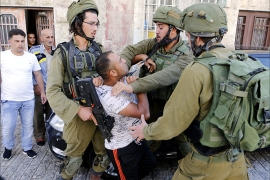 epa05549469 Israeli army soldiers restrain a Palestinian as he is being arrested following scuffling during raids on houses in the West Bank city of Hebron, 20 September 2016. Clashes in Hebron broke out after the most recent case of a Palestinian assailant being killed by the Israeli army on 20 September 2016.  EPA/ABED AL HASHLAMOUN