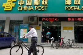 A man pushes his bicycle past a branch of China Post's Postal Savings Bank of China in Wuhan, Hubei province May 4, 2012. REUTERS/Stringer/File Photo CHINA OUT. NO COMMERCIAL OR EDITORIAL SALES IN CHINA