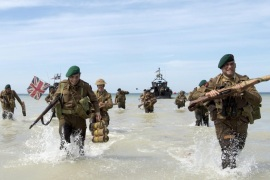 A handout image released by the British Ministry of Defence (MOD) shows people re-enacting marching onto the beach from a Landing Craft at the Normandy, France, 06 June 2014. More than 75,000 British Canadian and other Commonwealth Troops landed on the beaches of Normandy on 06 June 1944 alongside the United States and the Free French, in an Allied invasion of more than 130,000. Another 7,900 British troops were landed by Air. The invasion established a crucial second front in the Liberation of Europe from Nazi occupation, ultimately leading to victory for Allied Forces in 1945.  EPA/JAMIE PETERS RLC / HANDOUT
