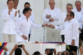 Colombian President Juan Manuel Santos (C-L) hands over a pin with the image of the dove of peace to Chief of Revolutionary Armed Forces of Colombia (FARC) Rodrigo Londono Echeverri (C-R), alias 'Timochenko', after the signing the peace agreement between Colombia's government and FARC to end over 50 years of conflict, in Cartagena, Colombia, 26 September 2016. The pact is the result of nearly four years of talks in Havana and was signed at a solemn ceremony in Cartag