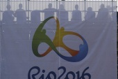 2016 Rio Olympics – Tennis – Olympic Tennis Centre – Rio de Janeiro, Brazil – 06/08/2016. Spectators are seen behind a banner with the 2016 Rio Olympics logo during a match. REUTERS/Toby Melville  FOR EDITORIAL USE ONLY. NOT FOR SALE FOR MARKETING OR ADVERTISING CAMPAIGNS.