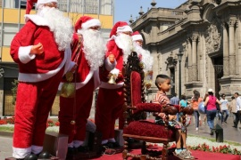 A child poses for a picture with Santa Claus figures, next to the government palace (R), in downtown Lima, Peru, December 11, 2016.  REUTERS/Mariana Bazo