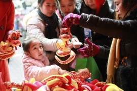 People buy plush toys depicting snakes in Shanghai January 23, 2013. The Lunar New Year, or the Spring Festival, begins on February 10 this year and marks the start of the Year of the Snake. REUTERS/Aly Song  (CHINA – Tags: SOCIETY)