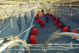 Detainees in orange jumpsuits sit in a holding area while watched by U.S. military police at the temporary Camp X-Ray, which was later closed and replaced by Camp Delta, inside Guantanamo Bay naval base in a January 11, 2002 file photo. President Barack Obama launched a final push on Tuesday to persuade Congress to close the U.S. military prison at Guantanamo Bay, Cuba, but lawmakers, opposed to rehousing detainees in the United States, declared his plan a non-starter.