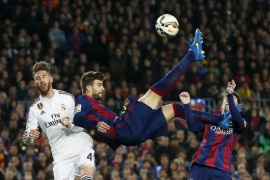 Barcelona's Gerard Pique (C) kicks the ball past Real Madrid's Sergio Ramos (L), as his team mate Lionel Messi looks on, during their Spanish first division