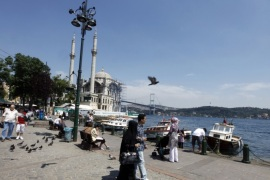 Tourists walk in front of the Ottoman era Ortakoy Mecidiye Mosque and Bosphorus Bridge in Istanbul July 5, 2011. Muslim but non-Arab Turkey has become a hot destination for Arab tourists and investors in recent years as Turkey has emerged as a regional power in the Middle East under Prime Minister Tayyip Erdogan's AK Party. Picture taken July 5, 2011. To match feature TURKEY-TOURISM/  REUTERS/Osman Orsal (TURKEY – Tags: TRAVEL POLITICS BUSINESS)
