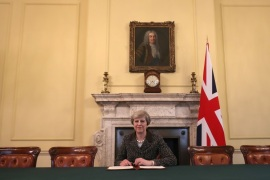British Prime Minister Theresa May in the cabinet, sitting below a painting of Britain's first Prime Minister Robert Walpole, signs the official letter to European Council President Donald Tusk invoking Article 50 and the United Kingdom's intention to leave the EU on March 28, 2017 in London, England. After holding a referendum in June 2016 the United Kingdom voted to leave the European Union, the signing of Article 50 now officially triggers that process. REUTERS/Chr