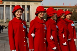 Hostesses pose in front of Great Hall of the People during the annual session of China's parliament, the National People's Congress (NPC), in Beijing, China  March 4, 2017. REUTERS/Tyrone Siu
