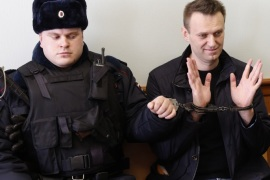 Russian opposition leader Alexei Navalny (R) shows his handcuffed hands during a hearing at the Moscow City Court