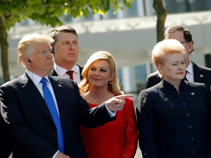 (L-R) U.S. President Donald Trump gestures next to Croatia's President Kolinda Grabar-Kitarovic, Germany's Chancellor Angela Merkel, France's President Emmanuel Macron, Belgium's Prime Minister Charles Michel and Luxembourg's Prime Minister Xavier Bettel during a NATO summit at their new headquarters in Brussels, Belgium, May 25, 2017. REUTERS/Jonathan Ernst?