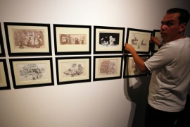 A man hangs cartoons by Palestinian caricaturist Naji al-Ali, who was assassinated in London 22 July 1987, during a media tour ahead of the 'Jerusalem Lives' exhibition at the Palestinian Museum on August 26, 2017, in the West Bank town of Birzeit, near Ramallah.The exhibition is scheduled to open on August 27 until December 15. / AFP PHOTO / ABBAS MOMANI / RESTRICTED TO EDITORIAL USE, MANDATORY CREDIT OF THE ARTIST, 'NAJI AL-ALI' TO ILLUSTRATE THE EVENT AS SPECIFIE
