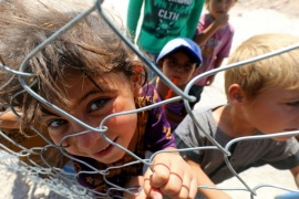 TOPSHOT – Displaced children from the Islamic State (IS) group's Syrian stronghold of Raqa, pose for a photo behind a fence at a camp in Ain Issa on August 22, 2017.  / AFP PHOTO / Delil souleiman        (Photo credit should read DELIL SOULEIMAN/AFP/Getty Images)