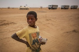 A local boy stands as a MINUSMA convoy pass by in the Gao region, Mali February 15, 2017. Each month MINUSMA organizes logistic convoys involving hundreds of civilians and military vehicles to supply remote UN bases in northern Mali. Picture taken February 15, 2017. MINUSMA/Sylvain Liechti handout via REUTERS   ATTENTION EDITORS – THIS PICTURE WAS PROVIDED BY A THIRD PARTY.