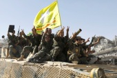Syrian Democratic Forces (SDF) fighters ride atop of military vehicle as they celebrate victory in Raqqa, Syria, October 17, 2017. REUTERS/Erik De Castro