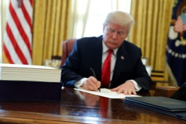 U.S. President Donald Trump signs sweeping tax overhaul legislation into law in the Oval Office at the White House in Washington, U.S. December 22, 2017.  REUTERS/Jonathan Ernst