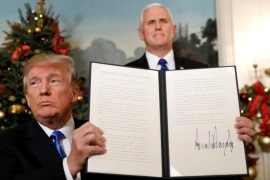 U.S. Vice President Mike Pence stands behind as U.S. President Donald Trump holds up the proclamation he signed that the United States recognizes Jerusalem as the capital of Israel and will move its embassy there, during an address from the White House in Washington, U.S., December 6, 2017.  REUTERS/Kevin Lamarque     TPX IMAGES OF THE DAY