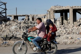Motorists ride a motorcycle past ruins of buildings destroyed during fightings with the Islamic State militants in Kobani, Syria October 11, 2017. Picture taken October 11, 2017.    REUTERS/Erik De Castro