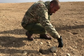ATTENTION EDITORS – VISUAL COVERAGE OF SCENES OF INJURY OR DEATH Local official Chokor Melhem Elias points out a human skull fragment, found in a recently unearthed mass grave in Sinjar, Iraq November 25, 2017. Picture taken November 25, 2017. REUTERS/Raya Jalabi