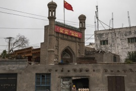 KASHGAR, CHINA – JUNE 28: A Chinese flag flies over a local mosque recently closed by authorities as an ethnic Uyghur woman sells bread at her bakery on June 28, 2017 in the old town of Kashgar, in the far western Xinjiang province, China. Kashgar has long been considered the cultural heart of Xinjiang for the province's nearly 10 million Muslim Uyghurs. At an historic crossroads linking China  to Asia, the Middle East, and Europe, the city has  changed under Chinese r