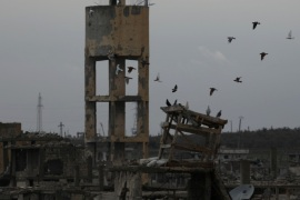 Birds fly above damaged buildings in a rebel-held area in the city of Deraa, Syria January 25, 2018. REUTERS/Alaa al-Faqir