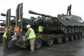 PALDISKI, ESTONIA – MARCH 22:  A crew secures a British Army Challenger 2 tank of the 5th Battalion The Rifles to a truck trailer after the tank and other heavy vehicles arrived by ship on March 22, 2017 at Paldiski, Estonia. British heavy tanks, light tanks, mobile artillery and other equipment unloaded at Paldiski today as part of a deployment by approximately 800 British combat troops taking part in the multinational NATO Enhanced Forward Presence battalion. NATO mem