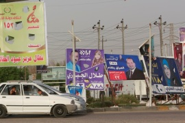 Vehicles drive near campaign posters of candidates ahead of parliamentary election, in Najaf, Iraq, April 20, 2018. Picture taken April 20, 2018. REUTERS/Alaa Al-Marjani