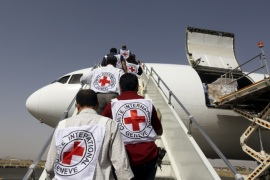Red Cross staffers board a plane carrying a shipment of emergency medical aid at Sanaa airport April 11, 2015. REUTERS/Khaled Abdullah