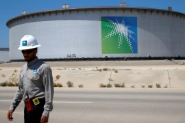 An Aramco employee walks near an oil tank at Saudi Aramco's Ras Tanura oil refinery and oil terminal in Saudi Arabia May 21, 2018. Picture taken May 21, 2018. REUTERS/Ahmed Jadallah