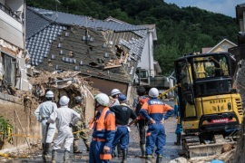 HIROSHIMA, JAPAN – JULY 09: Emergency services members wait by buildings destroyed by a landslide on July 8, 2018 in Kumano near Hiroshima, Japan. Over 100 people are now believed to have died during floods and landslides triggered by 'historic' levels of heavy rain across central and western parts of Japan while more than 50,000 rescuers are racing to find survivors as temperatures rise. Japan's Prime Minister Shinzo Abe warned on Sunday of a 'race against time' to rescue flood victims as almost 2 million people are subject to evacuation orders and tens of thousands remain without electricity and water. (Photo by Carl Court/Getty Images)