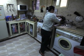 "Nahed, or ""Um Rania"", 52, prepares lunch in her kitchen at her home after she finished a shift driving a minibus in Cairo's Al Moqattam district March 4, 2014. Nahed, a widow whose husband died 21 years ago, bought a minibus and learned to drive after her street vending business failed. A supporter of Army Chief Field Marshal Abdel Fattah al-Sisi, she hopes the government can return stability to the country without any further violence. On March 8 activists around the"