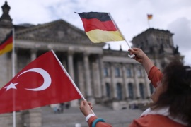 A demonstrator holds Turkish and German flags in front of the Reichstag, the seat of the lower house of parliament Bundestag in Berlin, Germany, June 1, 2016, as she protests against a disputed vote in Germany's parliament on Thursday, on a resolution that labels the killings of up to 1.5 million Armenians by Ottoman forces as genocide.  REUTERS/Hannibal Hanschke
